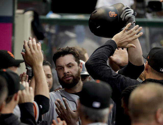 San Francisco Giants' Brandon Belt celebrates in the dugout after his two-run home run against the Los Angeles Angels during the second inning of a baseball game in Anaheim, Calif., Saturday, April 21, 2018. (AP Photo/Chris Carlson)