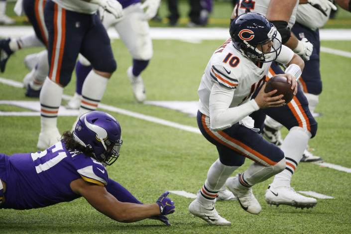 Chicago Bears quarterback Mitchell Trubisky (10) runs from Minnesota Vikings defensive tackle Hercules Mata'afa, left, during the second half of an NFL football game, Sunday, Dec. 20, 2020, in Minneapolis. (AP Photo/Bruce Kluckhohn)