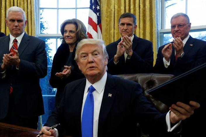 President Trump signs addition executive orders in the Oval Office on Saturday. (Photo: Jonathan Ernst/Reuters)