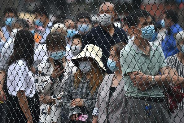 People wearing face masks gather at an outdoor area to take a swab test during mass testing for the COVID-19 coronavirus in Beijing.