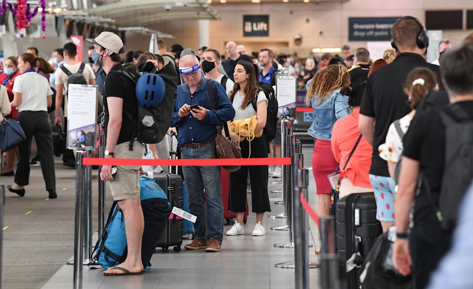 SYDNEY, AUSTRALIA - DECEMBER 18: Airline passengers wait in line to check in at Sydney's Kingsford Smith domestic airport on December 18, 2020 in Sydney, Australia. A cluster of Covid-19 cases on the northern beaches of Sydney has grown to 28, prompting NSW health officials to urge residents of affected suburbs to stay home. Traffic at Sydney Airport has increased as people rush to leave the city with several states imposing quarantine restrictions for New South Wales residents. (Photo by James D. Morgan/Getty Images)