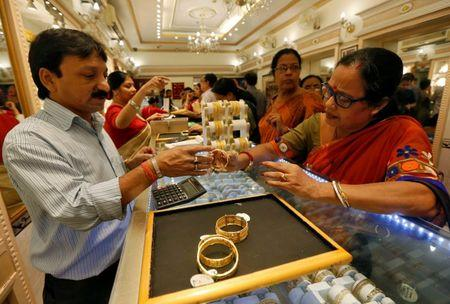 A salesman shows gold bangles to a customer at a jewellery showroom during Dhanteras in Kolkata