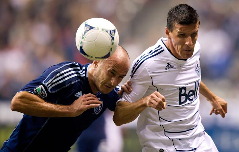 Sporting Kansas City's Aurelien Collin, left, of France, heads the ball and checks Vancouver Whitecaps' Sebastien Le Toux, also of France, into the sideline boards during first-half MLS soccer game action in Vancouver, British Columbia, Wednesday April 18, 2012. (AP Photo/The Canadian Press, Darryl Dyck)