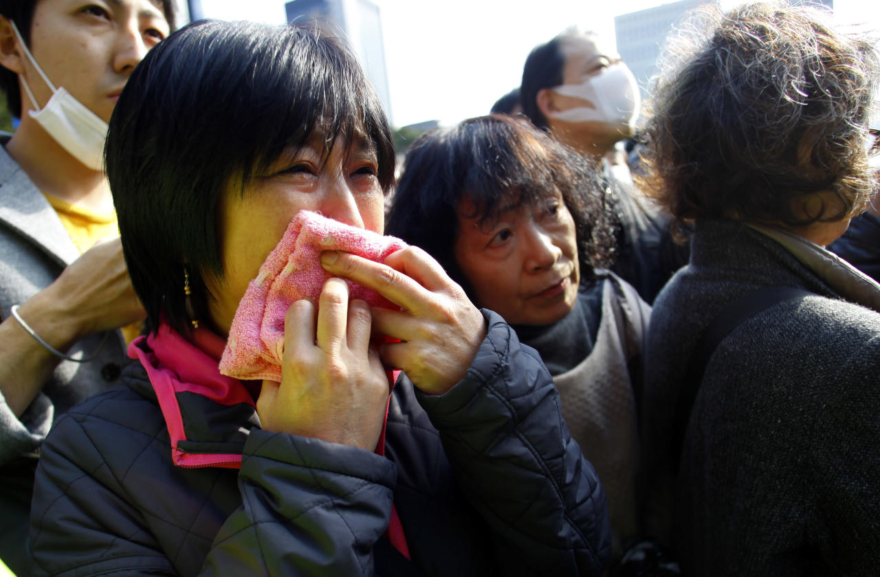 A woman weeps during a moment of silence to pay tribute to those who lost their lives in the March 11, 2011 earthquake and tsunami in Tokyo, Sunday, March 11, 2012. Through silence and prayers Sunday, people across Japan remembered the massive earthquake and tsunami that struck the nation one year ago, killing just over 19,000 people and unleashing the world's worst nuclear crisis in a quarter century. (AP Photo/Junji Kurokawa)