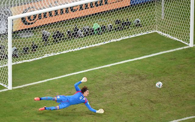 Mexico's goalkeeper Ochoa dives to stop the ball during their 2014 World Cup Group A soccer match against Brazil at the Castelao arena in Fortaleza