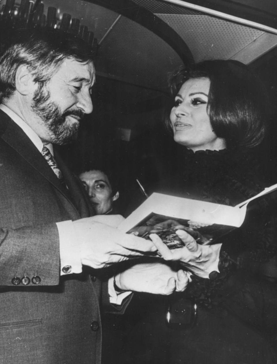 <p>French cartoonist Raymond Peynet talks to Sophia Loren over a copy of her book, <em>Cooking...with Love</em>, which he illustrated for her, aboard the boat Raffaelo, moored in Cannes, France in 1971.</p>