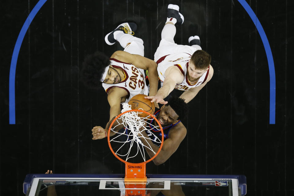 Philadelphia 76ers' Joel Embiid, center, goes up for a rebound against Cleveland Cavaliers' Jarrett Allen, left, and Dean Wade during the first half of an NBA basketball game, Saturday, Feb. 27, 2021, in Philadelphia. (AP Photo/Matt Slocum)