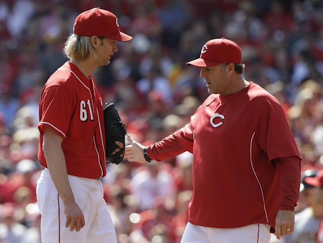Cincinnati Reds starting pitcher Bronson Arroyo (61) talks with pitching coach Bryan Price during the third inning of a baseball game against the Pittsburgh Pirates, Saturday, Sept. 28, 2013, in Cincinnati. (AP Photo/Al Behrman)