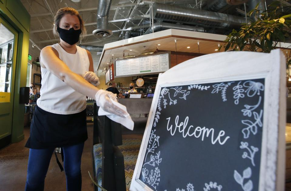 Laura Spencer, a recruiter at the corporate offices of the Fox Restaurant Concepts' Phoenix-based eateries, cleans off surfaces as she helps out at Flower Child restaurant as Arizona slowly relaxes restrictions due to the coronavirus. (AP Photo/Ross D. Franklin)