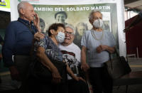 A 97 year old retired American soldier Martin Adler poses with Giulio, left, Mafalda, right, and Giuliana Naldi that he saved during a WWII at Bologna's airport, Italy, Monday, Aug. 23, 2021. For more than seven decades, Martin Adler treasured a back-and-white photo of himself as a young soldier with a broad smile with three impeccably dressed Italian children he is credited with saving as the Nazis retreated northward in 1944. The 97-year-old World War II veteran met the three siblings -- now octogenarians themselves -- in person for the first time on Monday, eight months after a video reunion. (AP Photo/Antonio Calanni)