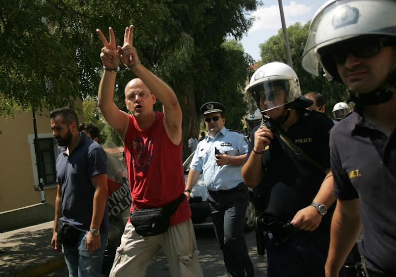 A handcuffed protester, arrested during an anti-government demonstration on the outskirts of Athens where TV transmitters are located, flashes a V sign upon his arrival at the court in Greek capital on Tuesday, July 30, 2013. It was latest protest in the wake of a decision by Greece's conservative-led government to shut down state broadcaster ERT in June, to open a new public TV and radio station with fewer staff later this year. (AP Photo/Angeliki Panagiotou, FOSPHOTOS)
