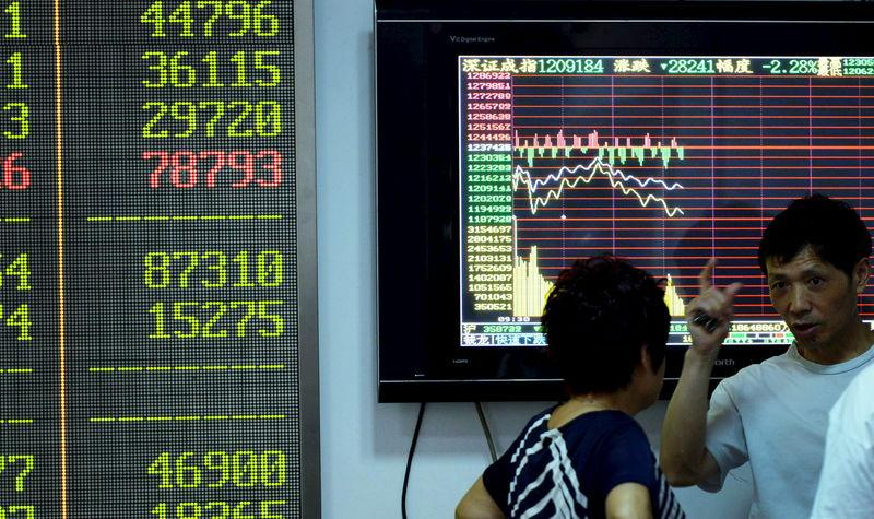 Investors talk in front of a screen showing stock information at a brokerage house in Hangzhou