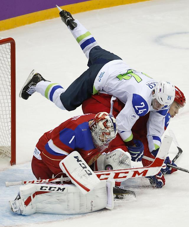Slovenia forward Rok Ticar falls over Russia goaltender Semyon Varlamov and defenseman Alexei Yemelin in the third period of a men's ice hockey game at the 2014 Winter Olympics, Thursday, Feb. 13, 2014, in Sochi, Russia. (AP Photo/Mark Humphrey)