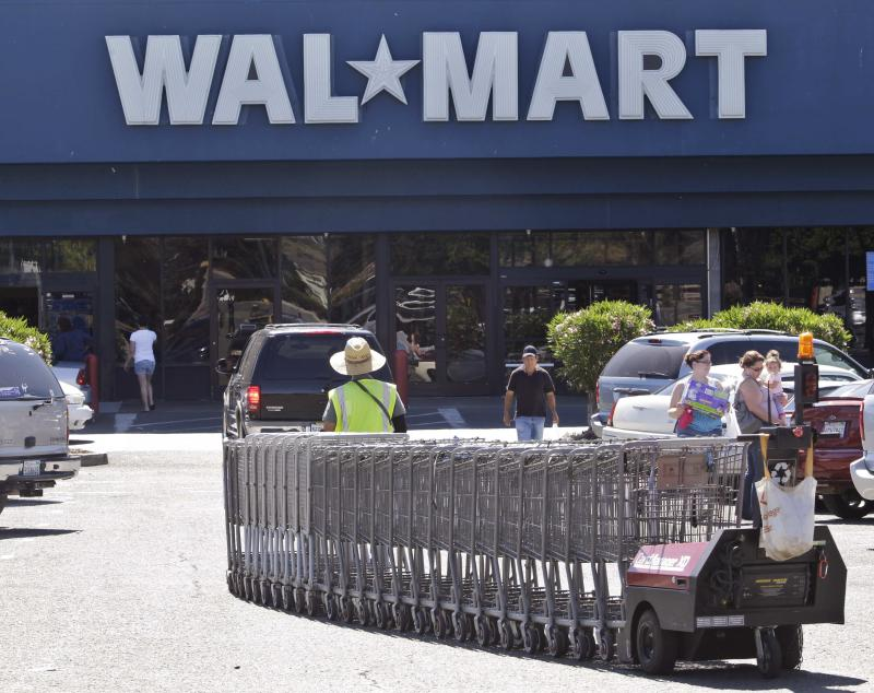 In this June 20, 2011 file photo, a Wal-Mart worker pulls carts at a Wal-Mart store in Pittsburg, Calif. A week before Halloween and two full months before Christmas, stores are desperately trying to outdo each other in hopes of drawing in customers worn down by the economy. Wal-Mart, the biggest store in the nation, joined the price wars Monday, Oct. 24, 2011, by announcing that it would give gift cards to shoppers if they buy something there and find it somewhere else cheaper.  (AP Photo/Paul Sakuma)