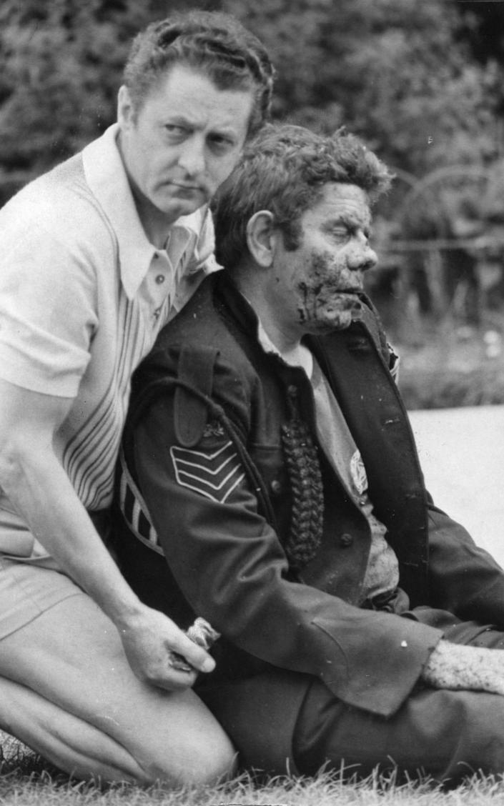 A sergeant in the band of the 1st Bn Royal Green Jackets, injured in the bandstand explosion, being comforted by a passer-by in Regent's Park