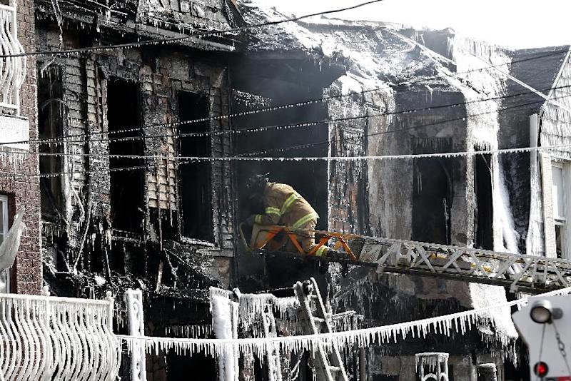 A firefighter inspects a charred home while standing on a ladder from a fire truck in Jersey City, N.J. on Thursday, March 6, 2014. Mayor Steven Fulop said a couple in their 80s and their two sons, who are in their 50s, were unaccounted for after the blaze on Grant Avenue was extinguished early Thursday. Authorities have not identified the two bodies that were found in the charred home. (AP Photo/Julio Cortez)