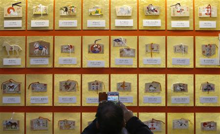 """A man takes pictures of """"Ema"""", small wooden plaques, displayed at Yasukuni Shrine in Tokyo January 1, 2014. REUTERS/Yuya Shino"""