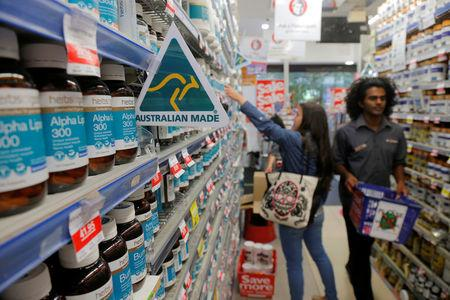 A shopper (L) browses for health products in an aisle stocked with vitamin supplements at a Mr Vitamins store in Sydney, Australia, March 9, 2017.  REUTERS/Jason Reed