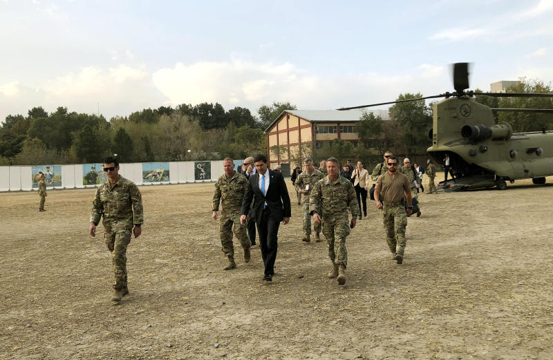 U.S. Defense Secretary Mark Esper, center, walks Gen. Scott Miller, right, chief of the U.S.-led coalition in Afghanistan, at the U.S. military headquarters in Kabul, Afghanistan, Sunday, Oct. 20, 2019. Esper arrived Sunday in Afghanistan, where stalled peace talks with the Taliban and persistent violent attacks by the insurgent group and Islamic State militants have complicated the Trump administration's pledge to withdraw more than 5,000 American troops. He told reporters traveling with him that he believes the U.S. can reduce its force in Afghanistan without hurting the counterterrorism fight against al-Qaida and the Islamic State group. (AP Photo/Lolita C. Balbor)