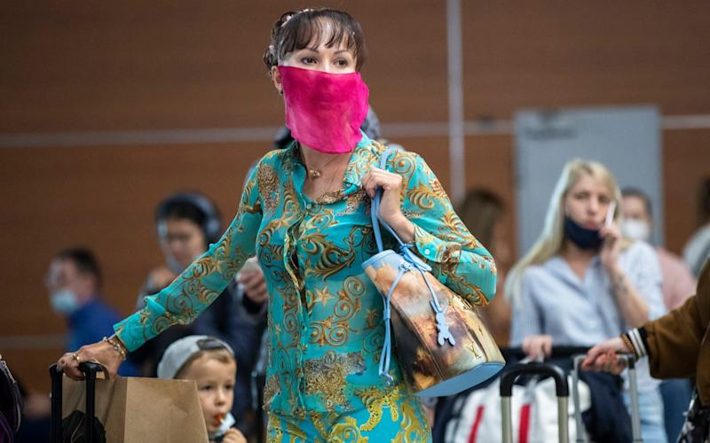 A woman wearing a face mask to protect against coronavirus waits in line to check-in at Sheremetyevo international airport, outside Moscow, Russia, Saturday, Aug. 1, 2020 - Pavel Golovkin/AP