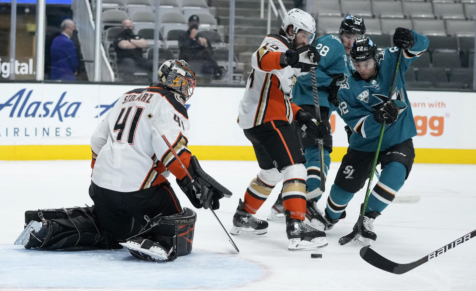 Anaheim Ducks goaltender Anthony Stolarz (41) blocks a shot by San Jose Sharks right wing Kevin Labanc (62) as center Adam Henrique (14) defends during the first period of an NHL hockey game Wednesday, April 14, 2021, in San Jose, Calif. (AP Photo/Tony Avelar)