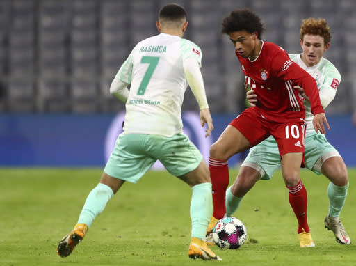 Bayern's Leroy Sane, centre, duels for the ball with Bremen's Joshua Sargent, right, and Bremen's Milot Rashica during the German Bundesliga soccer match between FC Bayern Munich and SV Werder Bremen in Munich, Germany, Saturday, Nov. 21, 2020. (AP Photo/Matthias Schrader)