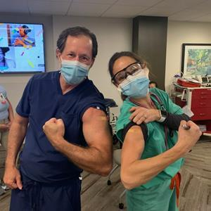 Jody Crane, MD, MBA, TeamHealth Chief Medical Officer, and Deb Vinton, MD, MBA, System Medical Director, TeamHealth Southeast Group, HCA Capital Division North, lead with their shoulders, receiving their first dose of the Pfizer-BioNTech vaccine.