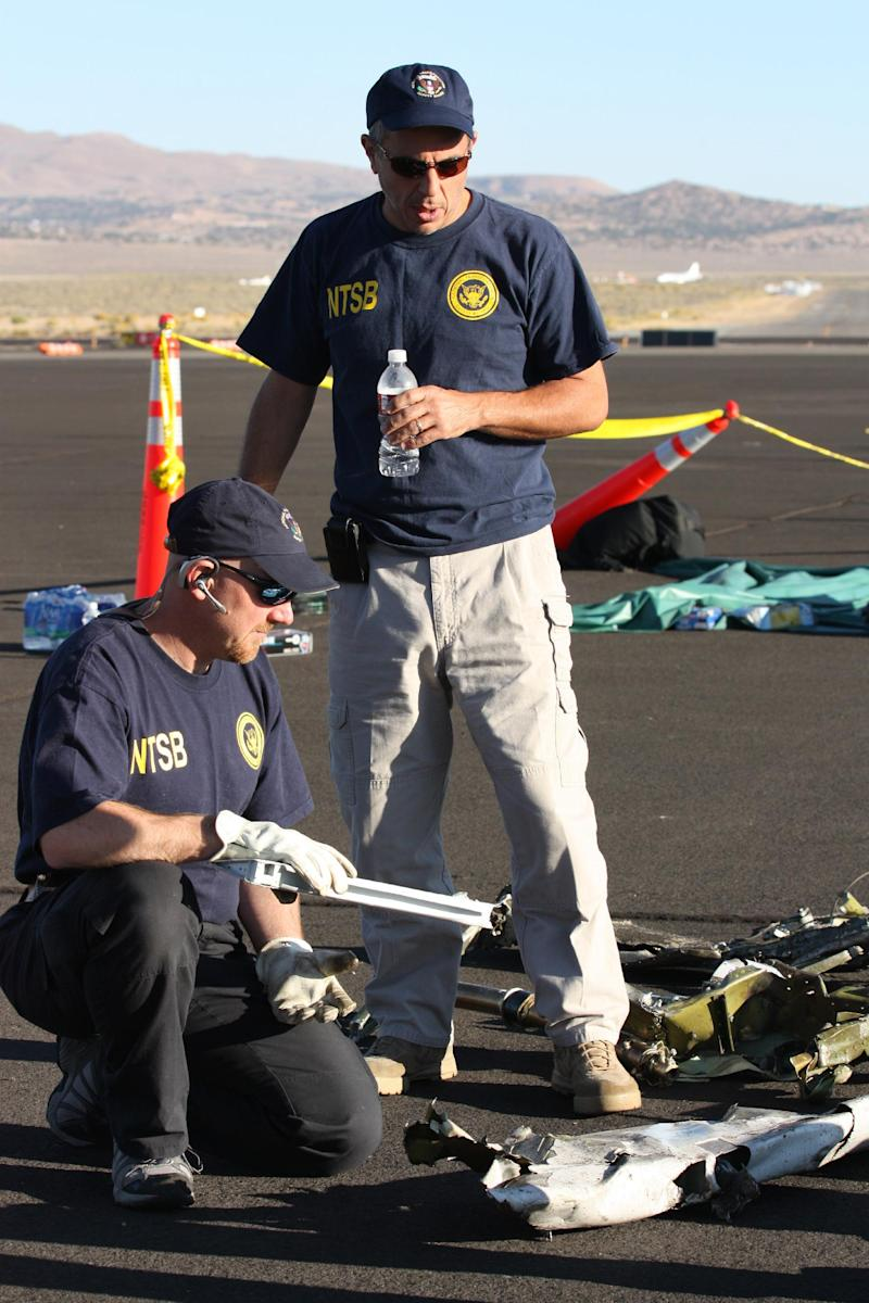 In this handout photo from the National Traffic Safety Board taken Sunday, Sept. 18, 2011 at an airfield in Reno, Nev., shows two NTSB officials looking at wreckage from Jimmy Leeward's plane that crash on Friday. Officials say nine people died.  (AP Photo/National Traffic Safety Board, HO)