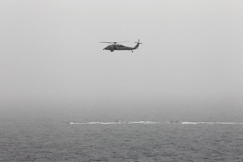 FILE PHOTO - Three Iranian Revolutionary Guard boats are seen near the U.S. aircraft carrier, USS George H. W. Bush while transiting Straits of Hormuz as U.S. Navy helicopter hovers over them during early hours of March 21, 2017. REUTERS/Hamad I Mohammed