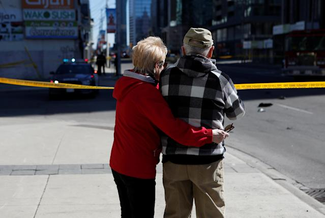 <p>A couple look down the road after an incident where a van struck multiple people at a major intersection in north Toronto, Ontario, Canada, April 23, 2018. (Photo: Chris Donovan/Reuters) </p>
