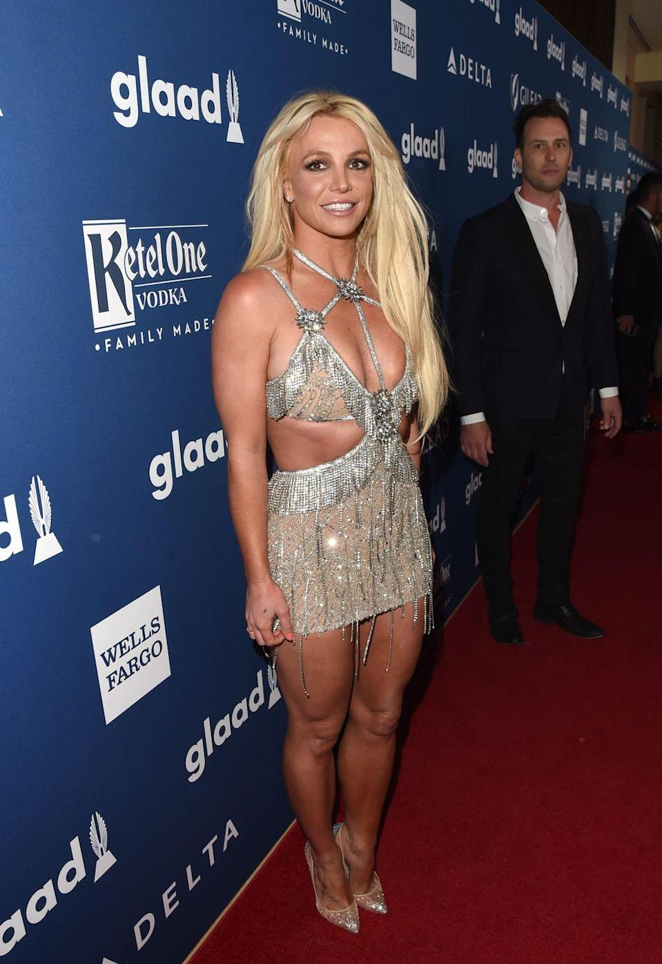 <p>Britney attends the GLAAD Media Awards in a strappy fringed metallic number with plenty of cutouts. She paired the ensemble with coordinating see-through heels. An icon!</p>