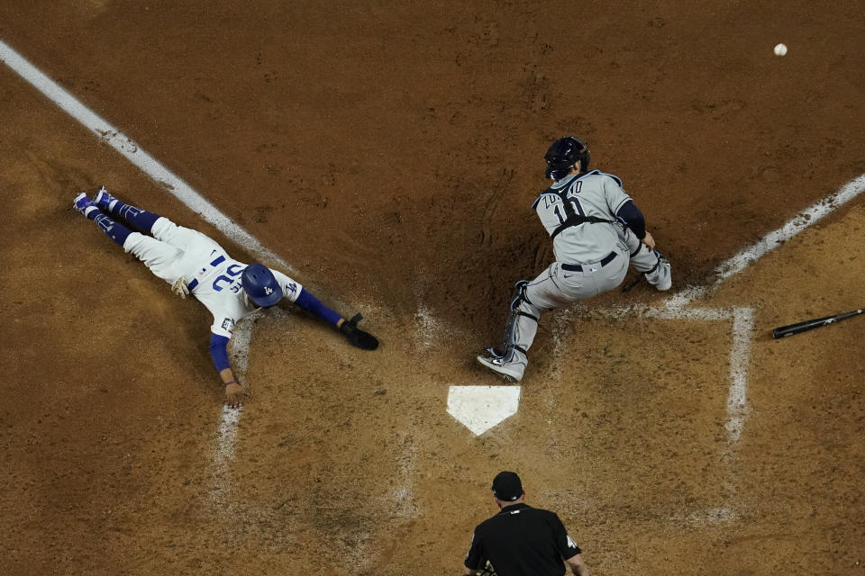 CORRECTS TO MOOKIE BETTS, INSTEAD OF AUSTIN BARNES - Los Angeles Dodgers' Mookie Betts scores past Tampa Bay Rays catcher Mike Zunino during the sixth inning in Game 6 of the baseball World Series on Tuesday, Oct. 27, 2020, in Arlington, Texas. (AP Photo/David J. Phillip)