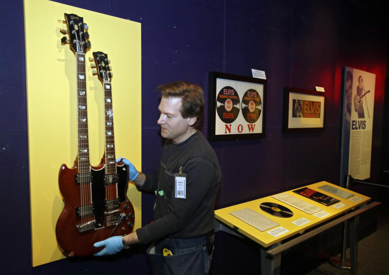 In this Nov. 25, 2013 photo, Andre Sepetavec installs a double-necked guitar in the Elvis exhibit at the Rock and Roll Hall of Fame and Museum in Cleveland. (AP Photo/Mark Duncan)