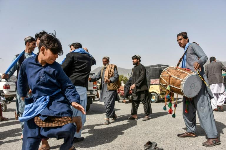 Men and youths in Kandahar dance as they celebrate the first day of 'reduction in violence' agreed between the Taliban, US and Afghan forces on February 22, 2020