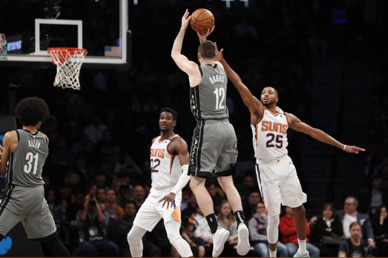 Phoenix Suns center Deandre Ayton (22) watches as Suns forward Mikal Bridges (25) defends Brooklyn Nets forward Joe Harris (12) who goes up for three points during the second half of an NBA basketball game, Monday, Feb. 3, 2020, in New York. The Nets defeated the Suns 119-97. (AP Photo/Kathy Willens)