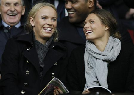 Danish tennis player Caroline Wozniacki (L) smiles as she takes her seat before the English Premier League soccer match between Liverpool and West Bromwich Albion at Anfield in Liverpool, northern England October 26, 2013. REUTERS/Phil Noble
