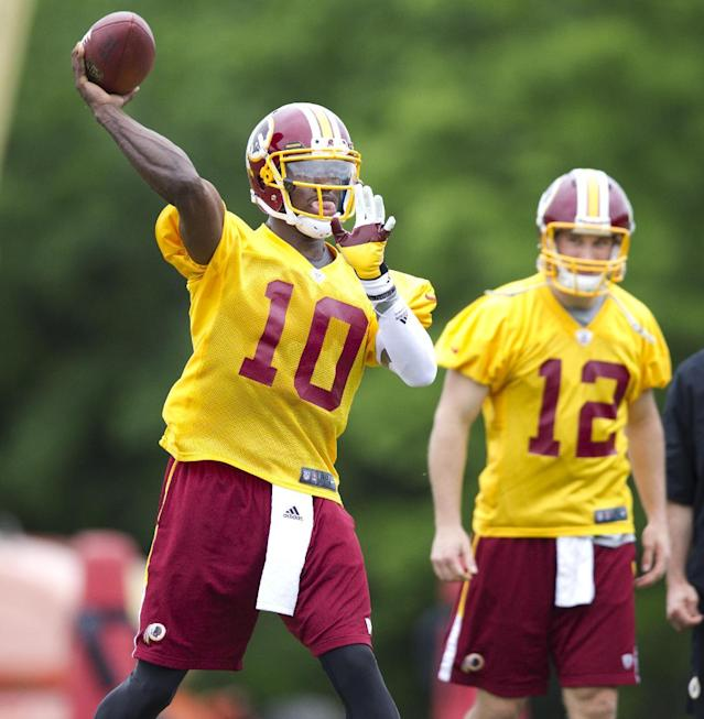CORRECTS TO LAST DAY, NOT FIRST DAY OF CAMP- Washington Redskins quarterback Robert Griffin III (10) throws in front of quarterback Kirk Cousin (12) during the last day of the team's rookie NFL football training camp at Redskins Park in Ashburn, Va., Sunday, May 6, 2012. (AP Photo/Manuel Balce Ceneta)