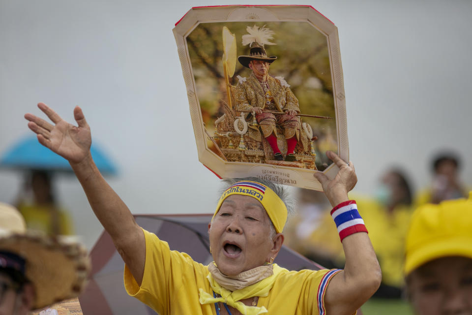 A supporter of the monarchy displays an image of King Maha Vajiralongkorn as she gather in front of the Grand Place in Bangkok, Thailand, Sunday, Nov. 1, 2020. Hundreds of royalists gathered close to the Grand Palace in which King Maha Vajiralongkorn is scheduled to visit for a Buddhist religious ceremony. (AP Photo/Wason Wanichakorn)