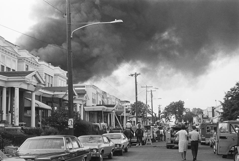 """Smoke billows over rowhouses in West Philadelphia on May 12, 1985 after the police bombed a residence home to members of the Black liberation group MOVE. Police on horseback and emergency vehicles block off a street as residents walk towards the scene.<span class=""""copyright"""">Bettmann Archive—Getty Images</span>"""
