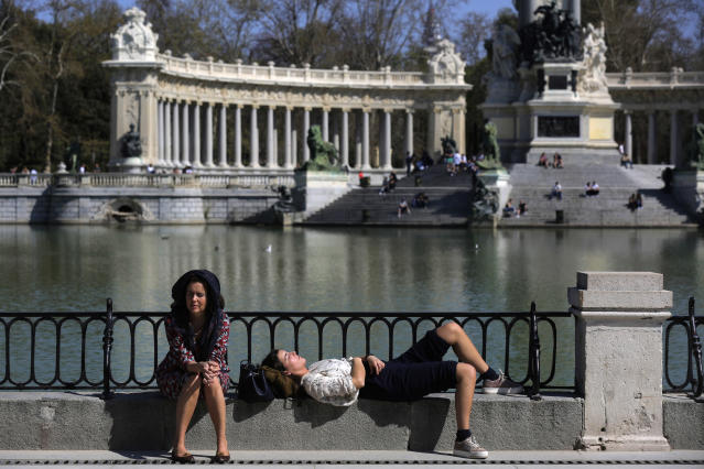 People enjoy the sun at the Retiro Park in Madrid, Spain, Saturday, March 14, 2020. Spanish Prime Minister Pedro Sanchez said his government will declare a two-week state of emergency from Saturday, giving itself extraordinary powers including the mobilization of the armed forces, to confront the COVID-19 outbreak. For some, especially older adults and people with existing health problems, it can cause more severe illness, including pneumonia. (AP Photo/Manu Fernandez)