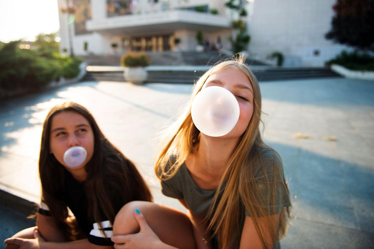 Teenagers chewing gum and blowing bubbles