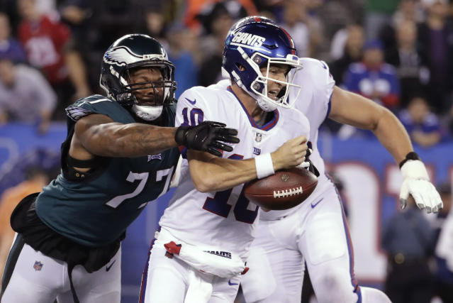 Philadelphia Eagles defensive end Michael Bennett (77) strips the ball from New York Giants quarterback Eli Manning during the first half of an NFL football game Thursday, Oct. 11, 2018, in East Rutherford, N.J. (AP Photo/Julio Cortez)