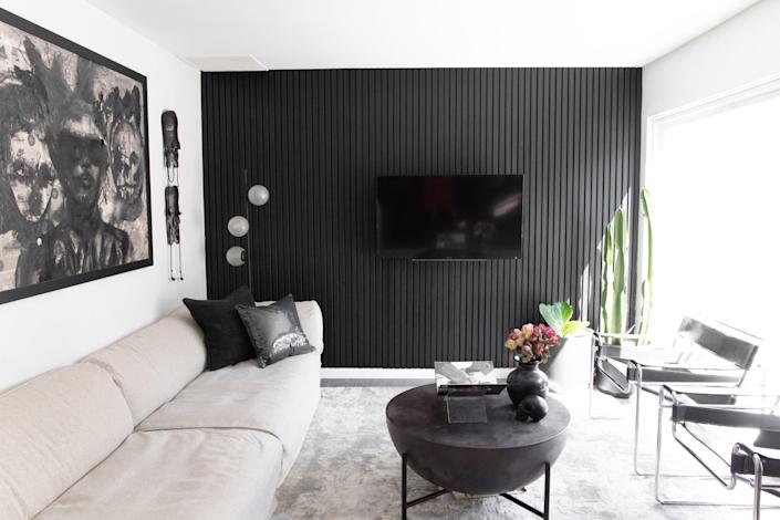 """These types of homes have exteriors that all look alike, so it was important for me to have some features that were our own and fun,"" Tiffany says. The accent wall is made of one-and-three-fourths inch oak slats that were nailed to the wall in one-inch gaps. The entire project was painted in Tricorn Black by Sherwin-Williams. The coffee table and floor lamp are from CB2, and the chrome Wassily side chairs were found on Chairish. The framed artwork was created by Julian and the masks are vintage."