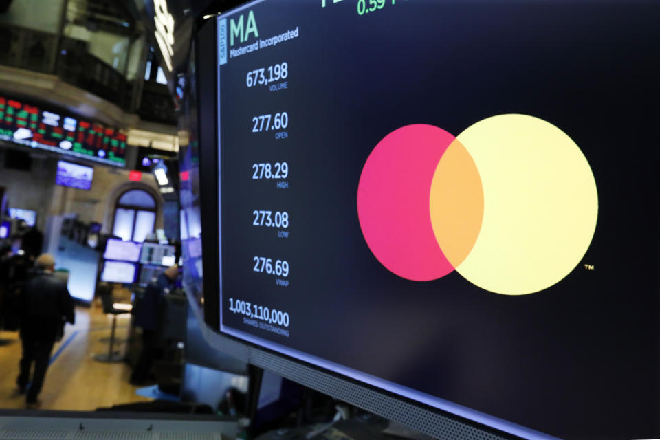 Mastercard logo appears above a trading post on the floor of the New York Stock Exchange. Photo: Richard Drew/AP