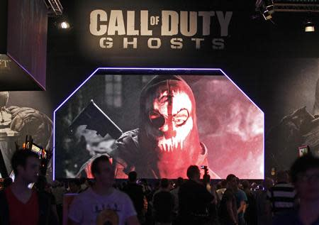 """Visitors look at a presentation of """"Call of Duty Ghosts"""" during Gamescom 2013 video games fair in Cologne"""