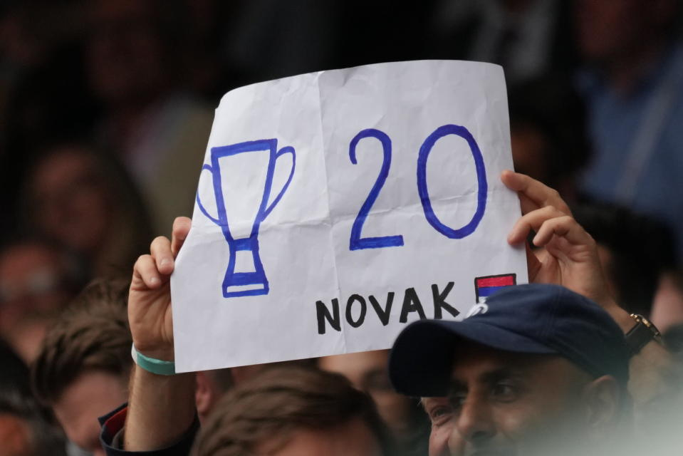 A fan holds a placard in support of Serbia's Novak Djokovic during the men's singles final match on day thirteen of the Wimbledon Tennis Championships in London, Sunday, July 11, 2021. (AP Photo/Alberto Pezzali)