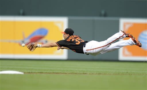 Baltimore Orioles second baseman Omar Quintanilla leaps in vain for a ball that went for a single by Oakland Athletics' Yoenis Cespedes during the first inning of a baseball game, Friday, July 27, 2012, in Baltimore. (AP Photo/Nick Wass)