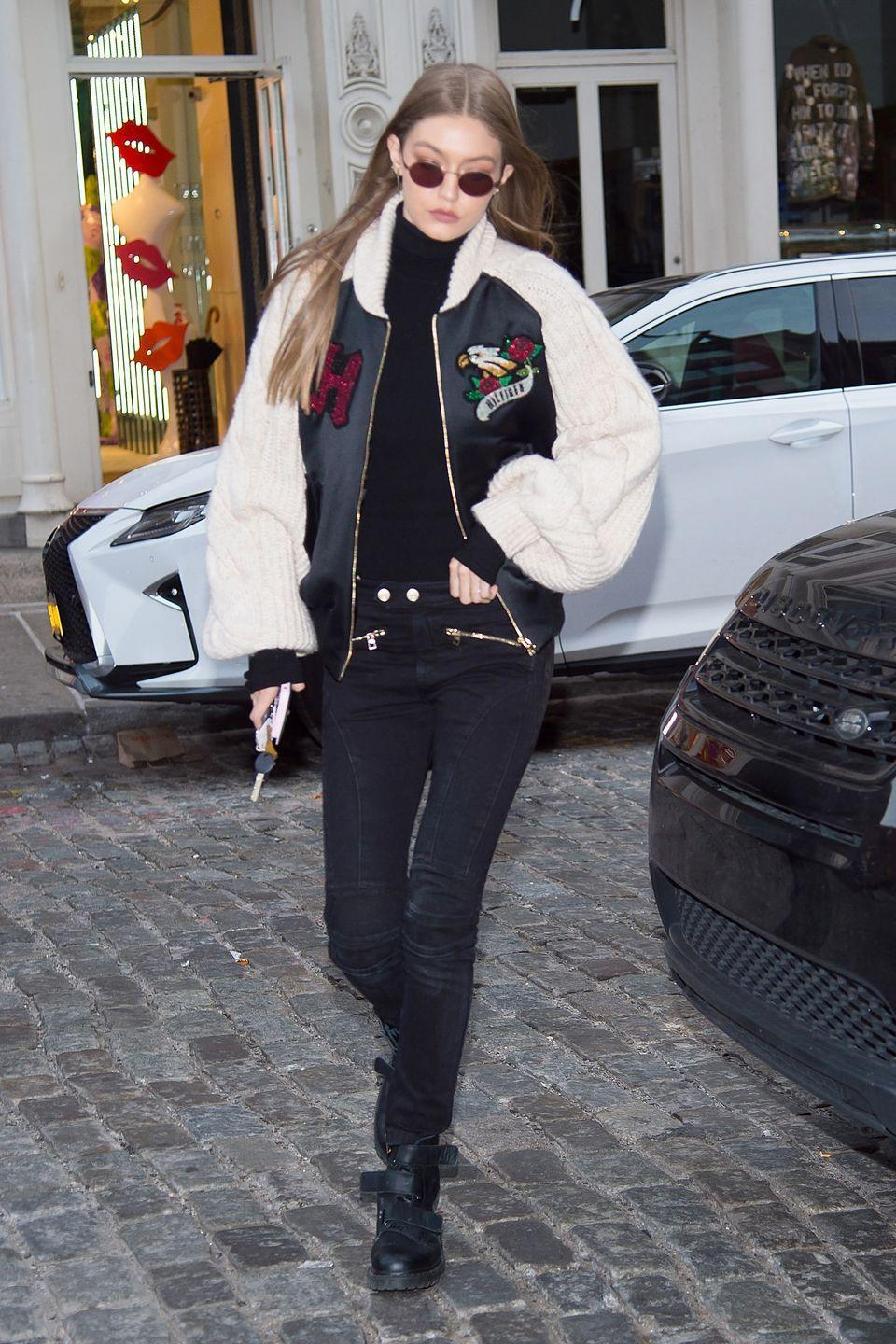 <p>In a Tommy Hilfiger sweater-bomber, black turtleneck, black jeans, Dr. Martens velcro boots and rounded sunglasses while out in New York.</p>