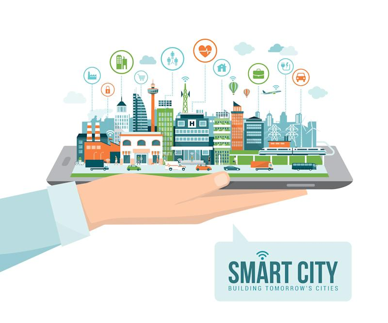 Hand holding a digital tablet with a contemporary smart city and apps icons: augmented reality and internet of things concept (Photo: elenabs via Getty Images)