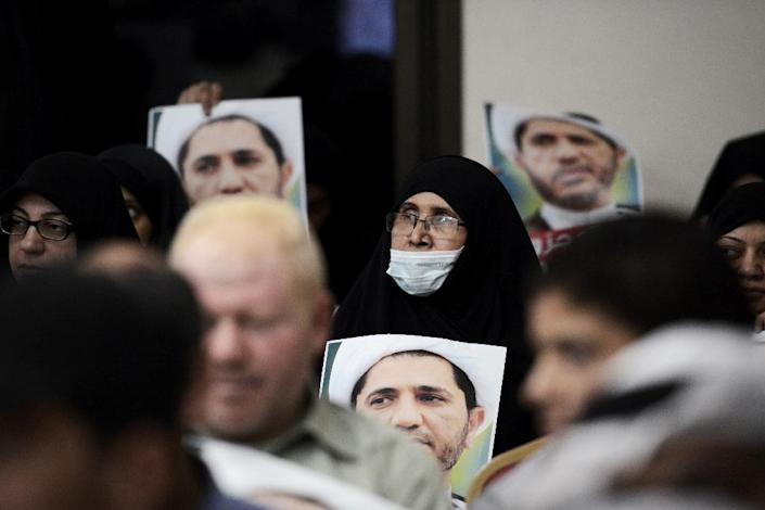 A Bahraini woman holds placards bearing the portrait of Sheikh Ali Salman, head of the Shiite opposition movement Al-Wefaq, during a protest on May 29, 2016 against his arrest in the village of Zinj (AFP Photo/Mohammed al-Shaikh)